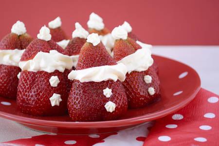 fresa: Santas fresa en la placa polka rojo y blanco sobre fondo rojo y blanco para la diversión, comida del partido festivo de la Navidad. Foto de archivo