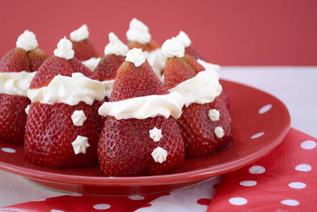 the strawberry: Strawberry Santas on red and white polka plate on red and white background for fun, cute Christmas festive party food.