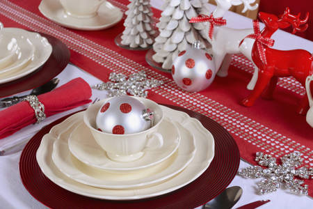 fine china: Festive red and white Christmas Table Setting with fine china place setting, reindeers and holiday ornaments and decorations, closeup.