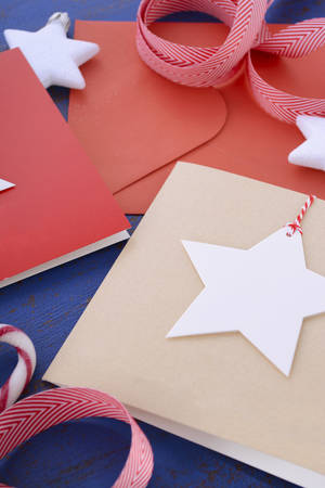 nautral: Writing Christmas and Holiday cards, with red and nautral kraft paper cards, pen and decorations on dark blue wooden table, closeup.