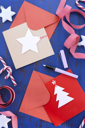 nautral: Writing Christmas and Holiday cards, with red and nautral kraft paper cards, pen and decorations on dark blue wooden table.