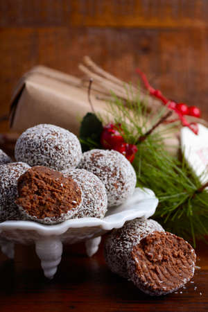 gift wrapping: Traditional Christmas Rum Ball candy spotlighted in festive setting with rustic style gifts and decorations on dark vintage wood background. Stock Photo