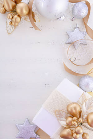 above 25: White and gold theme festive Christmas background with decorated borders including gifts and decorations on a rustic white wood table.