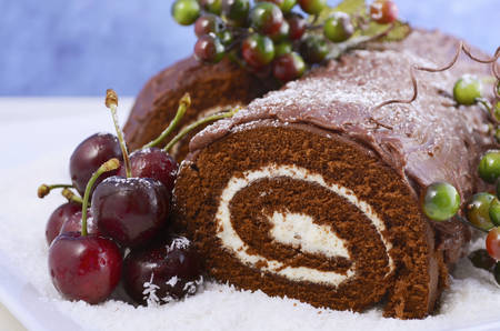 yule log: Christmas Yule Log, Buche de Noel, chocolate cake with branch, fresh cherries and festive berry decorations on a white serving platter, closeup.