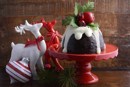 Traditional Christmas Plum Pudding on red cake stand with reindeer ornaments against a dark wood background.