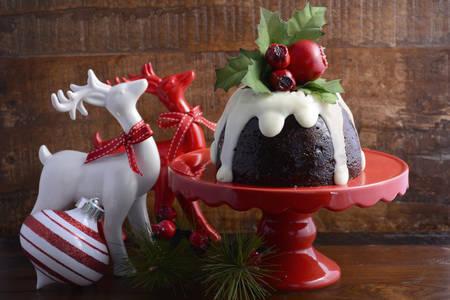 weihnachtskuchen: Traditionelle Weihnachts Plum Pudding auf rotem Etagere mit Rentiere Ornamente vor einem dunklen Holz Hintergrund.