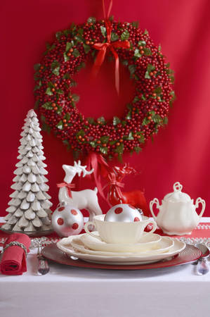 fine china: Festive red and white Christmas Table Setting with fine china place setting, reindeers and holiday ornaments and decorations. Stock Photo