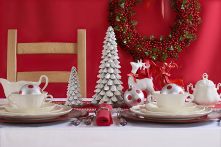 christmas decorations: Festive red and white Christmas Table Setting with fine china place setting, reindeers and holiday ornaments and decorations. Stock Photo