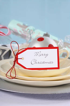 fine china: Modern Christmas table place setting with fine china and silver charger plates on white tablecloth and white tree branch centerpiece with stripe birds against a pale blue backdrop, closeup. Stock Photo