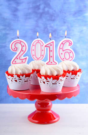 cakestand: Happy New Year cupcakes with lit 2016 candles on a red cakestand white table against a blue background. Stock Photo