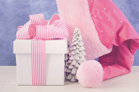 pink christmas: Feminine twist to Christmas holiday giving with Female Santa Hat with pink and white gift box on white table, with applied retro style filters.