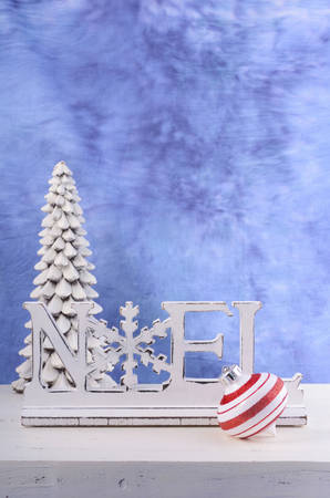 mantel: Modern Christmas mantel decorations with wooden Noel word against a blue and white background, with copy space for your text here.