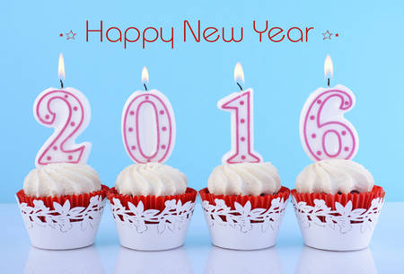 january 1: Happy New Year cupcakes with lit 2016 candles on white table against a blue background, with sample greeting text. Stock Photo