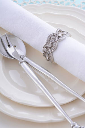 fine china: Elegant holiday table place setting with vintage napkin ring and cutlery closeup on fine china plate for Christmas, Thanksgiving or New Year celebrations. Stock Photo