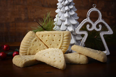 Traditional Christmas Petticoat Tails shortbread cookies with holiday ornaments on dark wood rustic background setting.