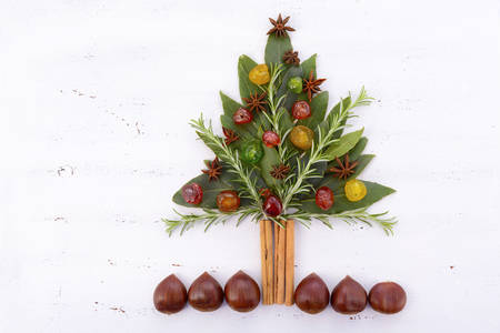 glace: Festive Cooking Concept with bay leaves, rosemary sprigs, cinnamon sticks, chestnuts, star anise and glace cherries in the shape of a Christmas Tree, on a shabby chic white rustic wood table.