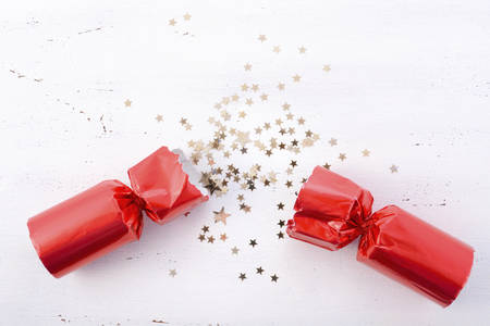 Festive surprise concept with opened red bon bon Christmas cracker and glitter stars on white wood table with copy space for your text here.