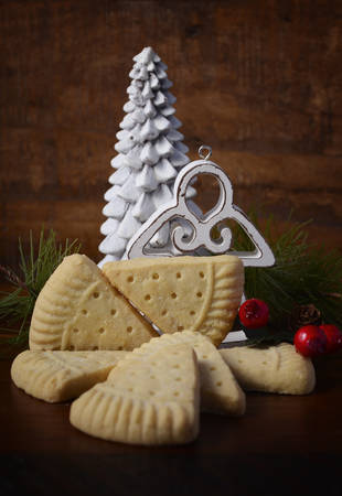 petticoat: Traditional Christmas Petticoat Tails shortbread cookies with holiday ornaments on dark wood rustic background setting. Stock Photo