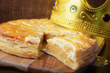 twelfth night: Epiphany Twelfth Night Cake, Almond Galette des Rois, Cake of the Kings, on dark wood rustic background. Stock Photo