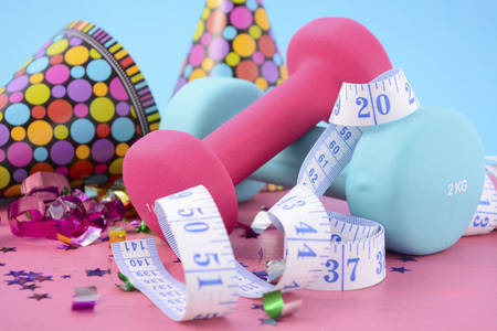 weight loss plan: New Year Exercise Resolution with dumbbells and party decorations on white and blue background. Stock Photo