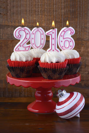 cakestand: Happy New Year 2016 Cupcakes with lit candles on red cakestand against a dark wood rustic background.