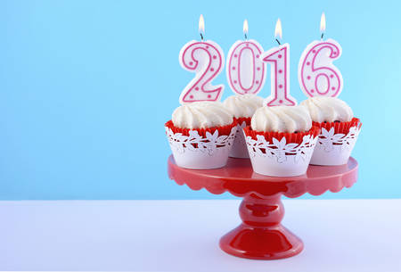 celebrate: Happy New Year cupcakes with lit 2016 candles on a red cakestand white table against a blue background with copy space for your text here.