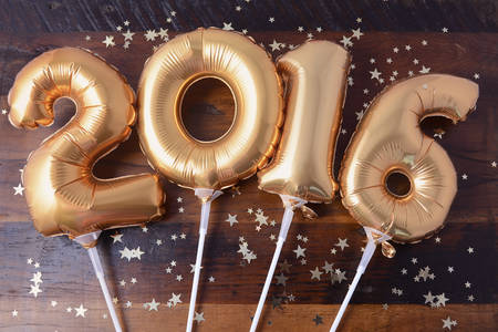 new years: Happy 2016 gold New Year Balloons with glitter stars on dark wood table background.