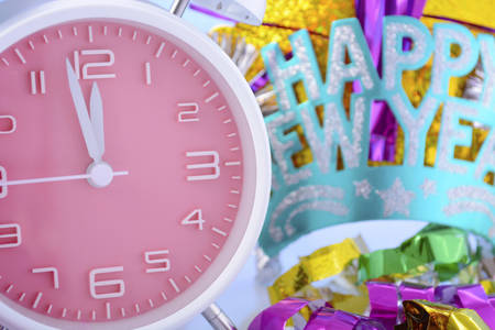 12 o clock: Happy New Year bright coloured clock and party hats and decorations.