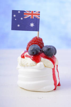 australia day: Australian mini pavlova and flag, close up, in red, white and blue them for Australia Day or national holiday party food treats.