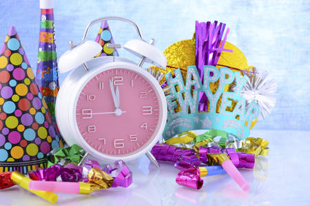 holiday maker: Happy New Year bright coloured clock and party hats and decorations.