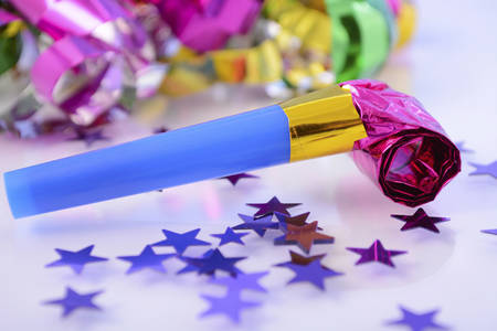 noise maker: Happy New Year party decorations with stars and noise maker, closeup.