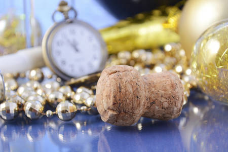 fob: Happy New Year party celebration with ballon, champagne glasses, decorations and pocket fob watch at nearly midnight, closeup on champagne bottle cork.