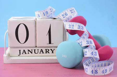 Happy New Year Fitness Resolution with pink and blur dumbbells and tape measure with white block calendar for January 1st.