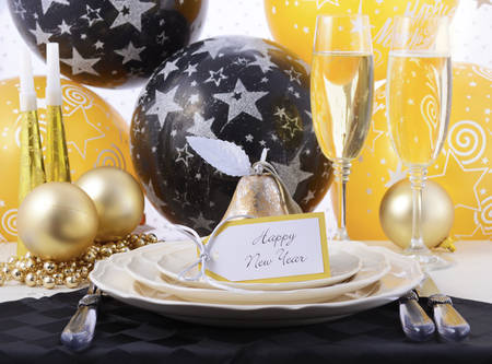 place setting: Happy New Year black, gold and white dinner party table place setting. Stock Photo
