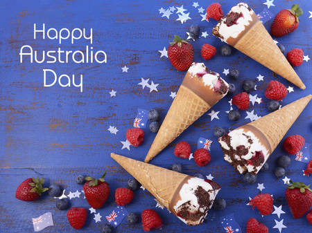 australia day: Happy Australia Day party ice cream cones with berry fruit and flags on a blue wood background, overhead with copy space.