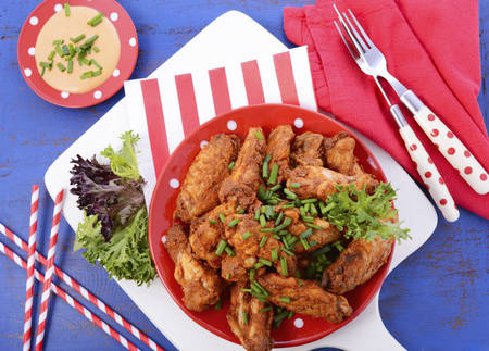 above 25: BBQ setting with spicy chicken wings with red, white and blue color theme.