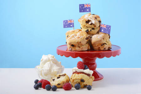 scone: Happy Australia Day morning tea with fruit scones on red cake stand with fresh fruit and cream on white wood table with blue background, with sample text.