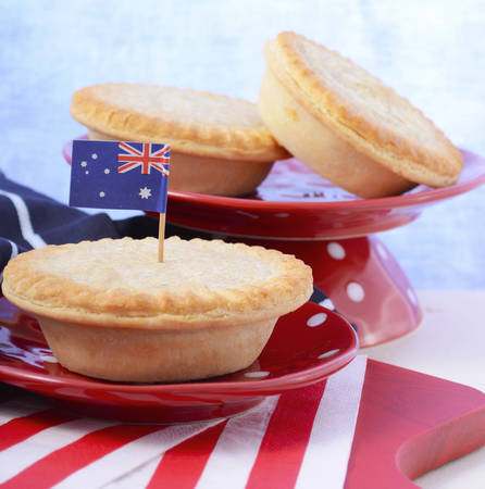 meat pie: Traditional Australian Meat Pies for Australia or Anzac Day holiday party food, in red, white and blue setting.