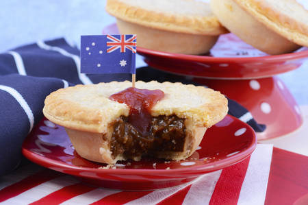 anzac: Traditional Australian Meat Pies for Australia or Anzac Day holiday party food, in red, white and blue setting.