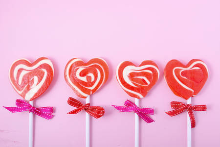 Happy Valentines Day candy with red heart shape lollipops on pink wood background.