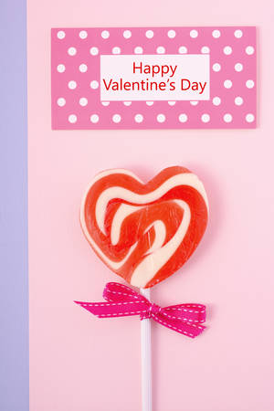 ard: Happy Valentines Day candy with red heart shape lollipop on pink wood background with polka dot greeting ard and sample text.