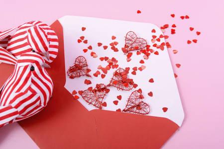love letter: Feliz día de San Valentín abrió el sobre carta de amor con adornos amor de aves en el fondo de madera de color rosa. Foto de archivo