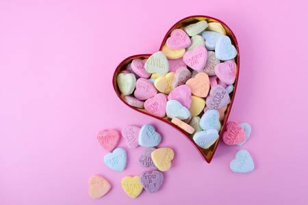 Happy Valentines Day snoep met rode hart vorm lollipop op roze hout achtergrond, met een kopie ruimte.