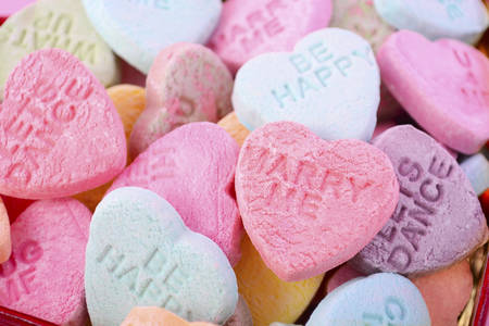 confectionery: Happy Valentines Day conversation candy closeup background. Stock Photo