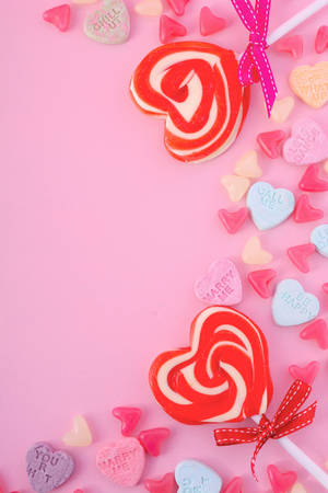 Happy Valentines Day Background with candy and red heart shape lollipops on pink wood background. Stock Photo