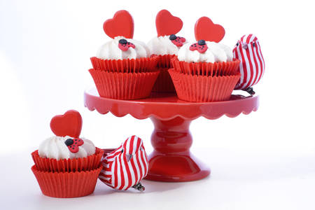 mini: Red and white Valentine cupcakes with hearts and love bug decorations on red cake stand with love bird ornaments against a white background.