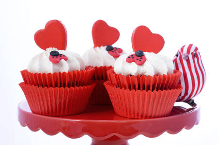 supper: Red and white Valentine cupcakes with hearts and love bug decorations on red cake stand with love bird ornament against a white background, closeup. Stock Photo