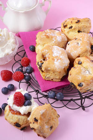 above 25: Morning or afternoon tea with English style fruit scones with cream and fresh fruit on pink background.