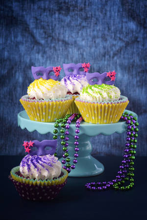 red velvet cupcake: Mardi Gras cupcakes with small mask toppers made from confectionery sugar, against a vivid blue background.