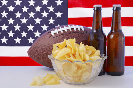 football party: American football with beer and chips on white wood table with USA stars and stripes flag background. Stock Photo